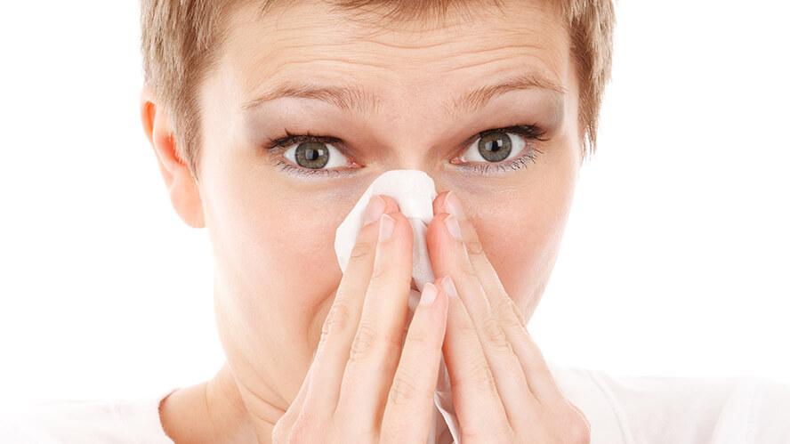 Frau putzt ihre Nase