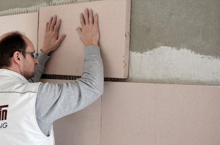 Handwerker bringt die Klimaplatte zur Innendämmung an