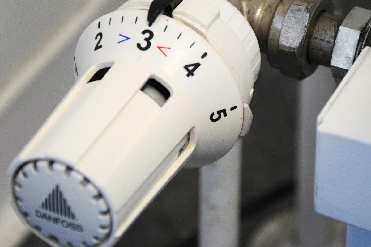 Thermostat an einer Heizung steht auf Stufe Drei